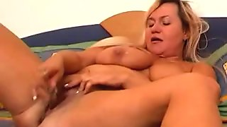A busty mom plays with a dildo for her camera totting